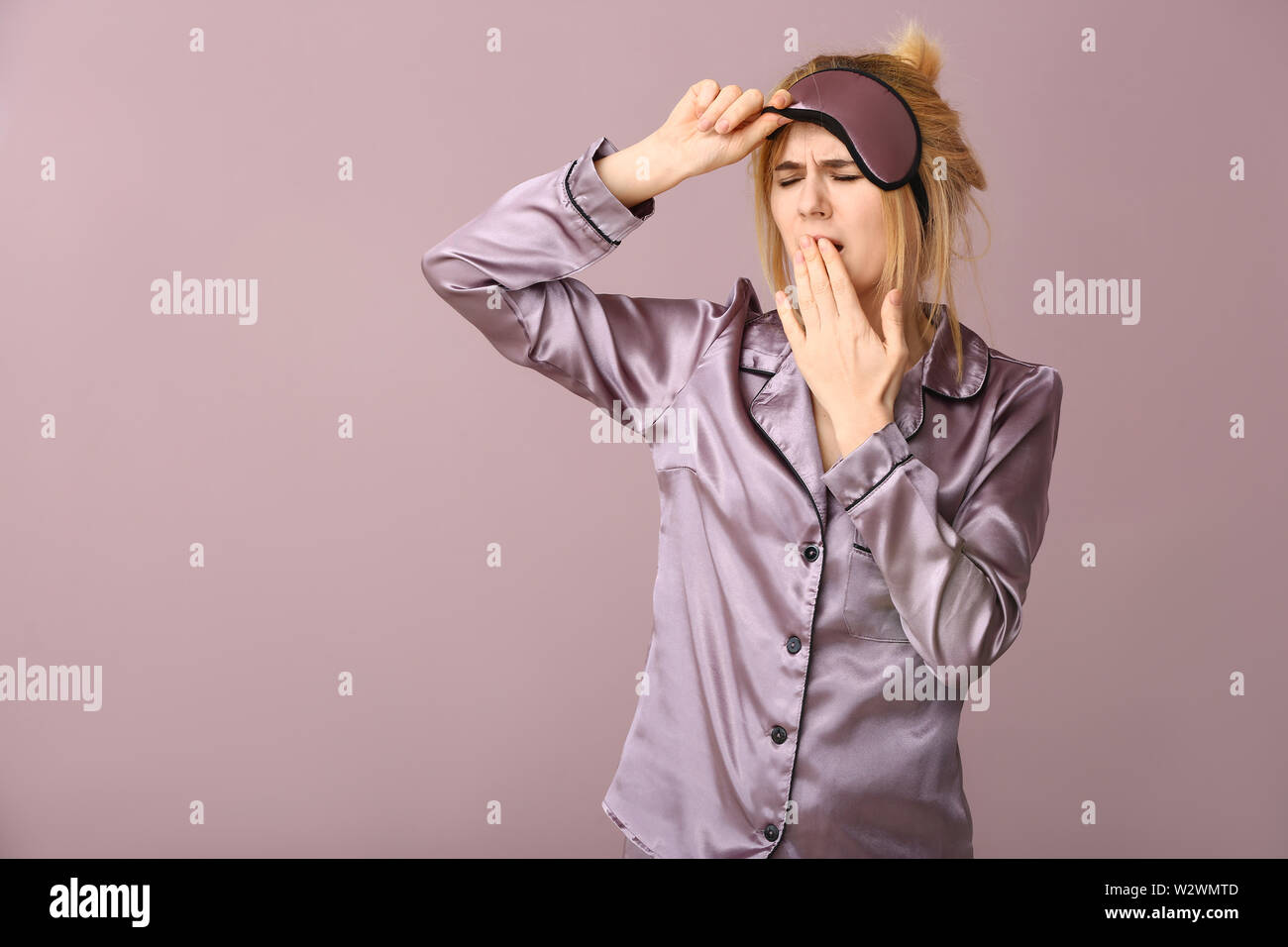 Sleepy woman with mask on color background - Stock Image
