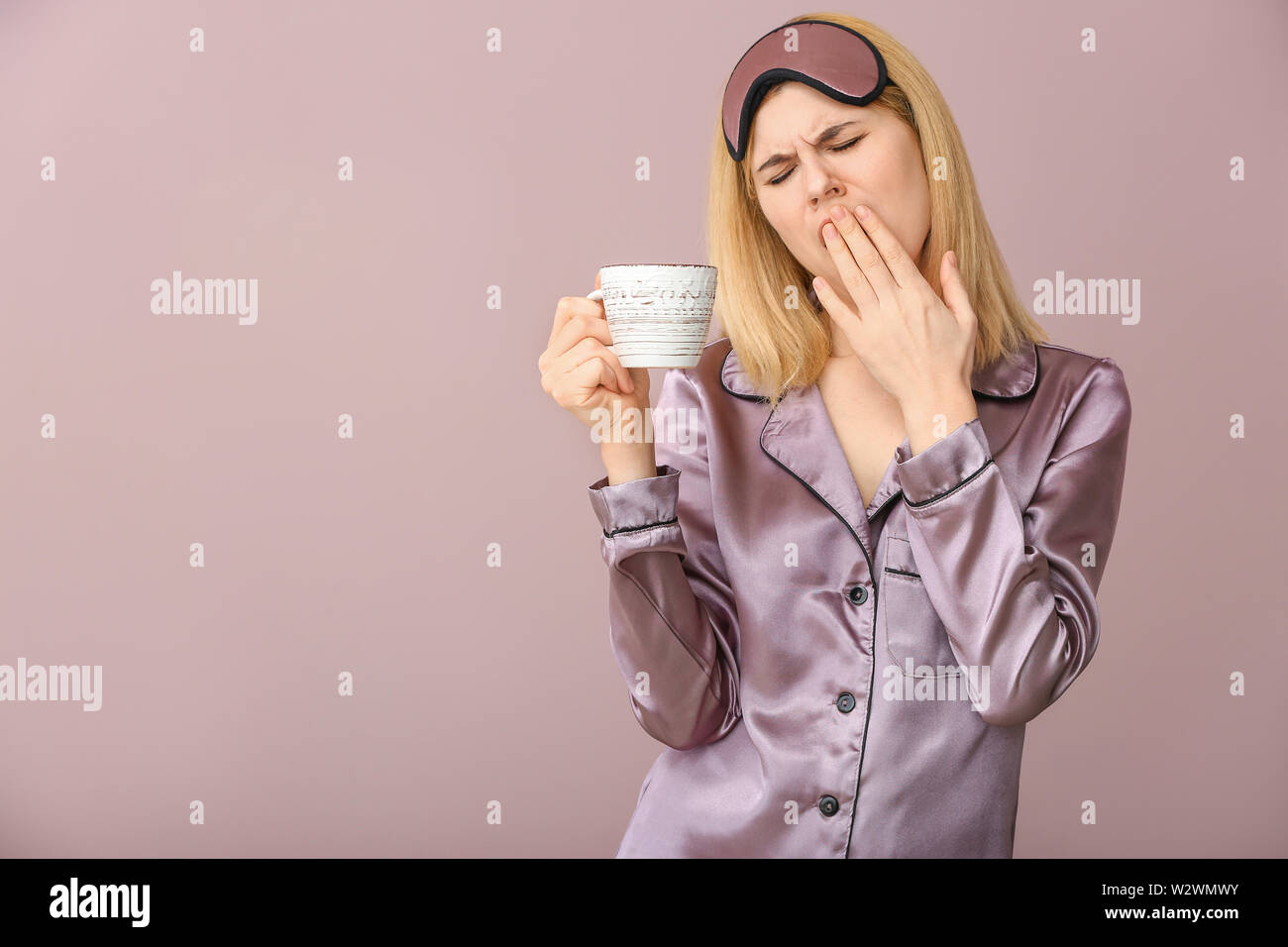 Sleepy woman with cup of coffee and mask on color background - Stock Image