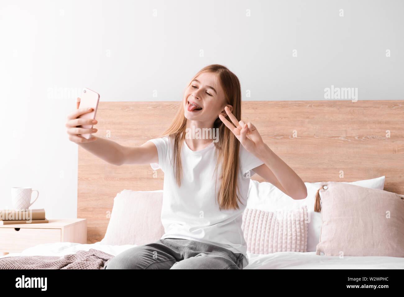 Cute Teenage Girl Taking Selfie In Bedroom At Home Stock Photo Alamy