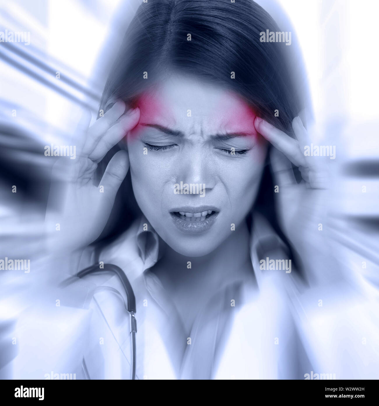 Young woman with a pounding headache or migraine standing clutching her temples with an expression of pain, monochrome image with selective red color to temples and blur effect around her face - Stock Image