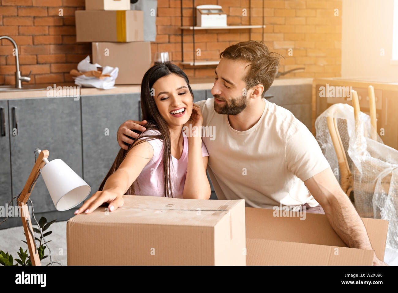 Young couple unpacking things after moving into new house Stock Photo
