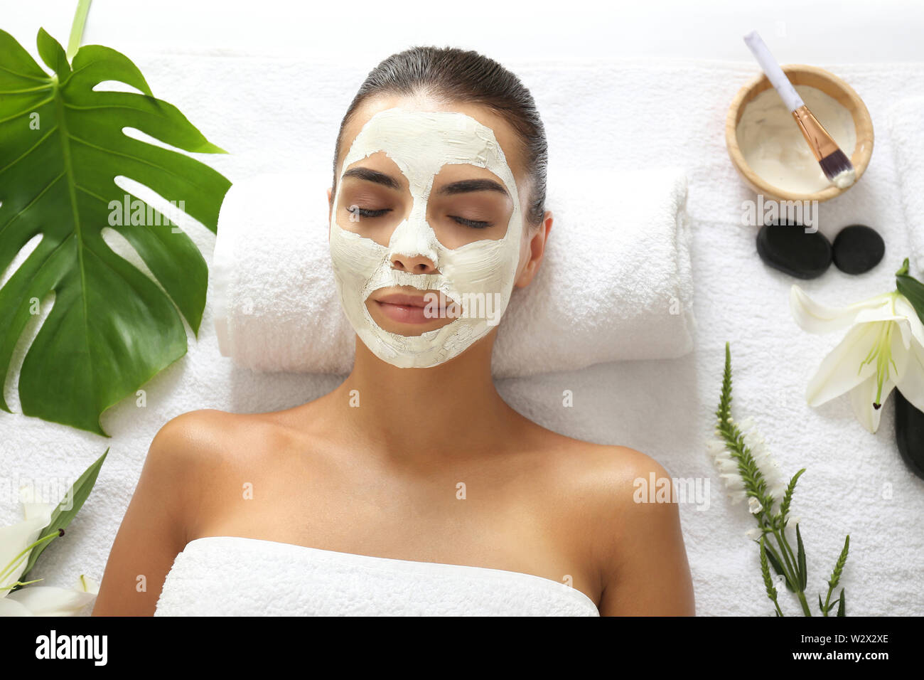 Beautiful Young Woman With Facial Mask Relaxing In Spa Salon Stock Photo Alamy