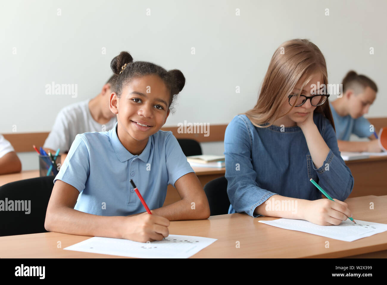 Teenage girls passing school test in classroom - Stock Image