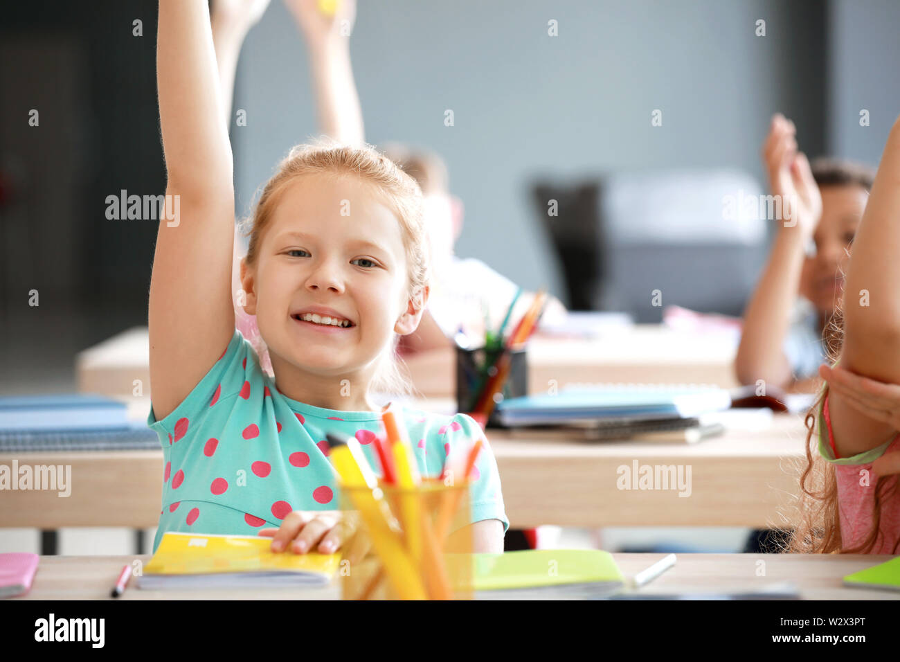 Cute little girl raising hand during lesson in classroom - Stock Image