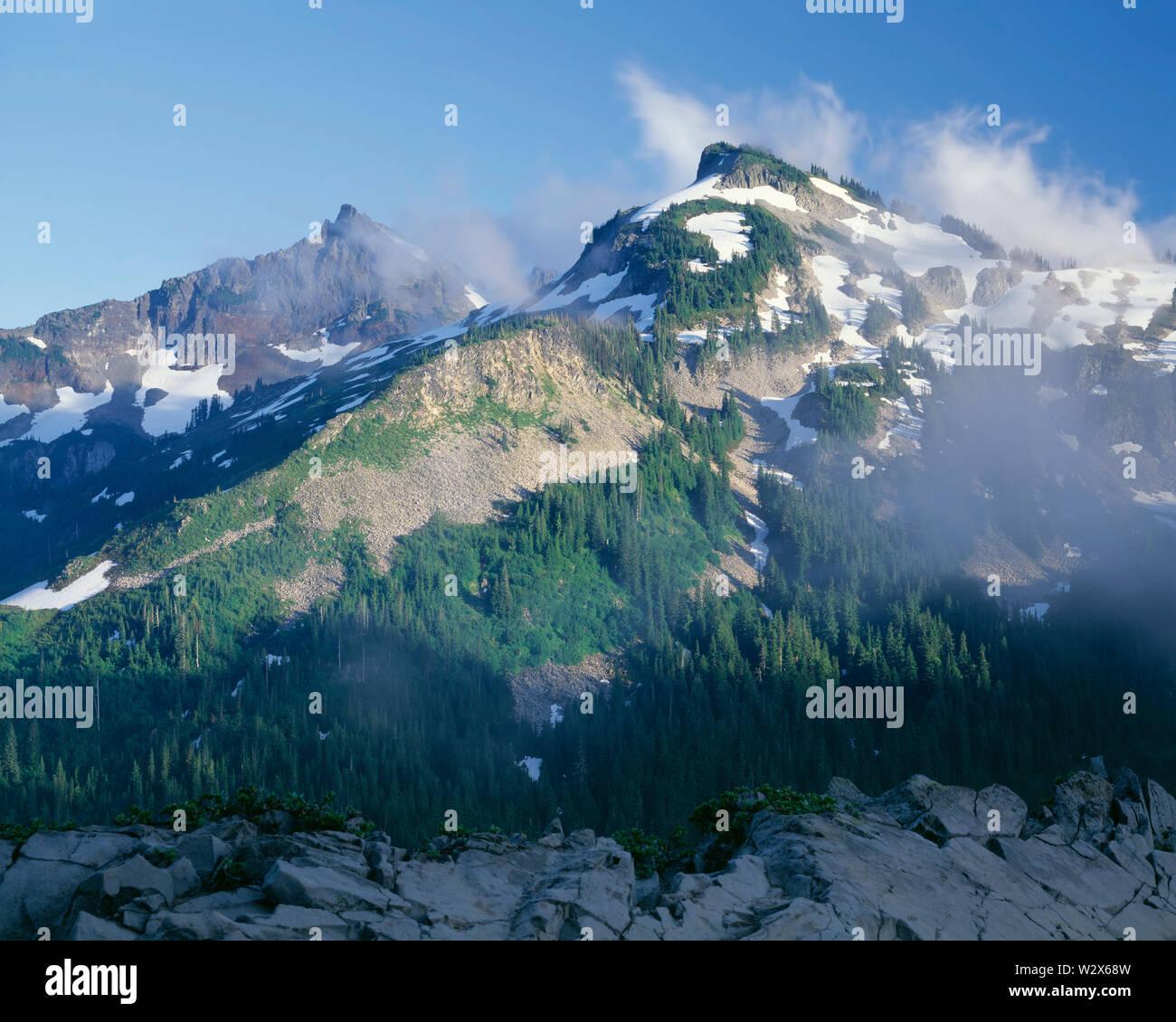 USA, Washington, Mt. Rainier National Park, Evening light on Unicorn Peak and other peaks of  the Tatoosh Range with swirling clouds. - Stock Image