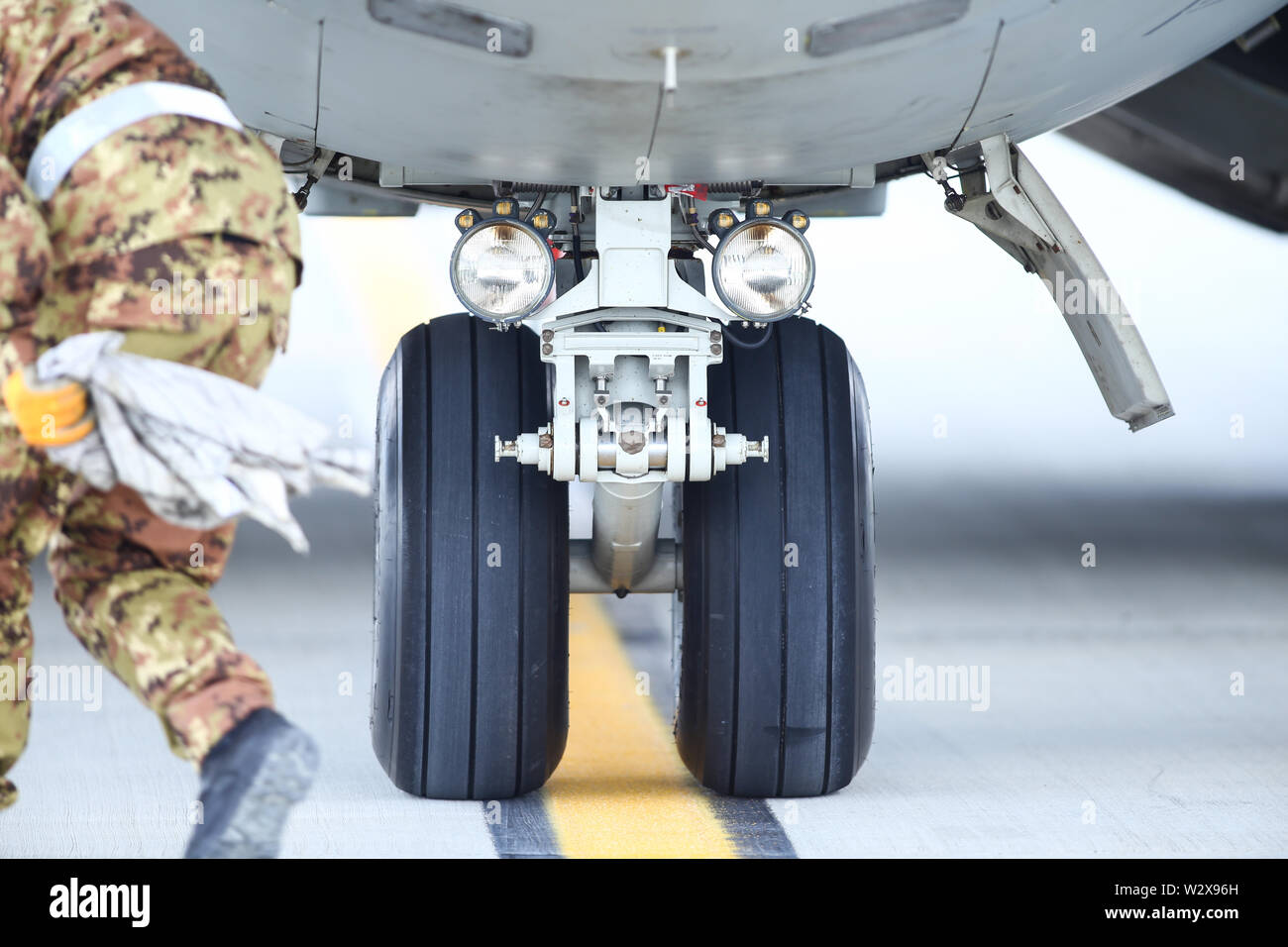 An army mechanic is inspecting the landing gear of a military cargo plane. - Stock Image