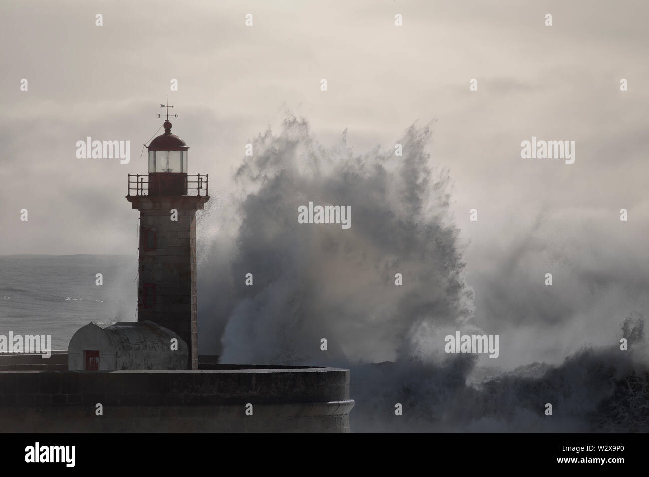 Soft backlit big wave splash. Old pier and lighthouse of Douro river mouth. - Stock Image