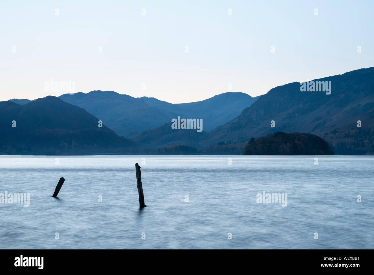 Beautiful long exposure landscape image of Derwent Water in Lake District during Autumn Fall sunrise with soft pastel colors - Stock Image