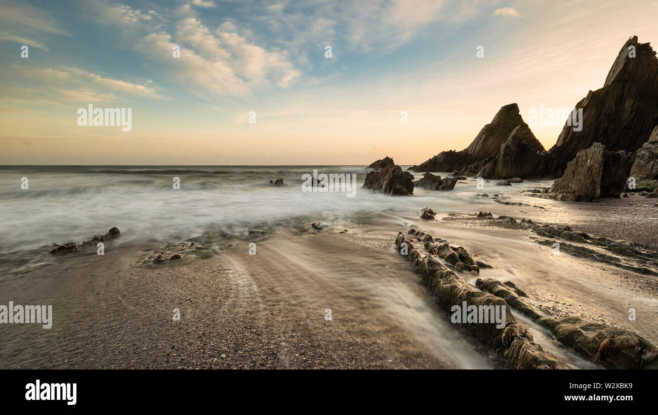 Beautiful sunset landscape image of Westcombe Beach in Devon England with jagged rocks on beach and stunning cloud formations - Stock Image