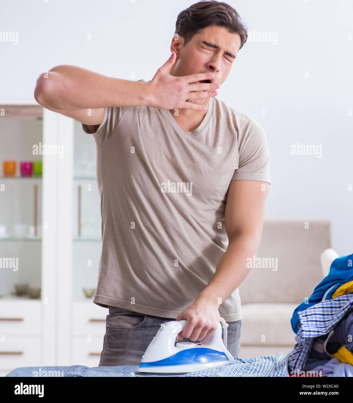 The young man husband doing clothing ironing at home - Stock Image