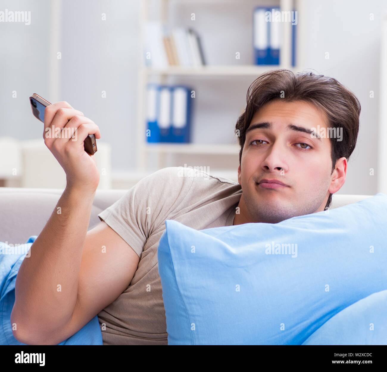 The man addicted to his mobile phone in bed - Stock Image