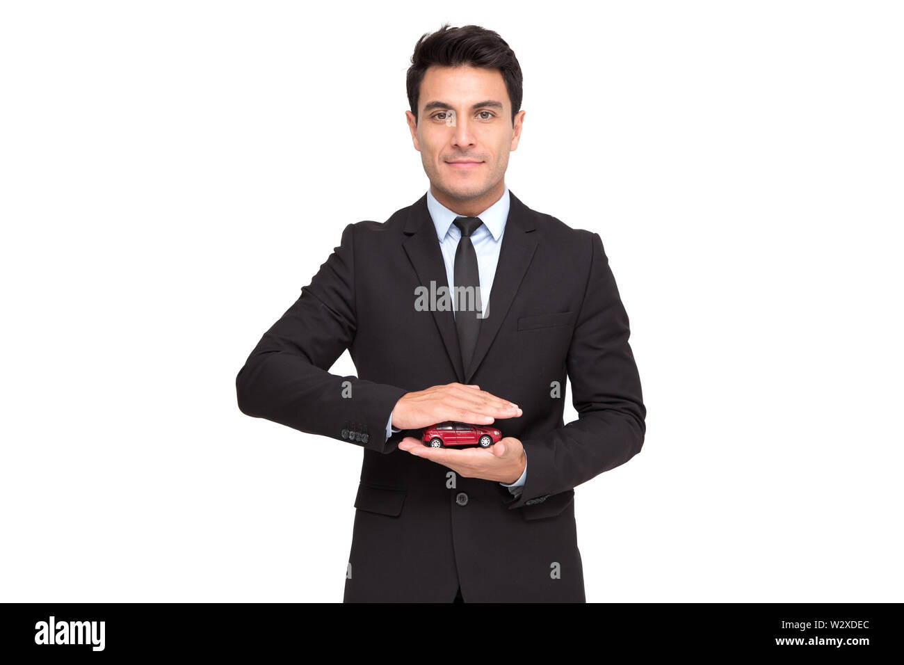 Portrait of a charming businessman dressed in suit holding toy car while standing isolated over white background, Car insurance and car services conce - Stock Image