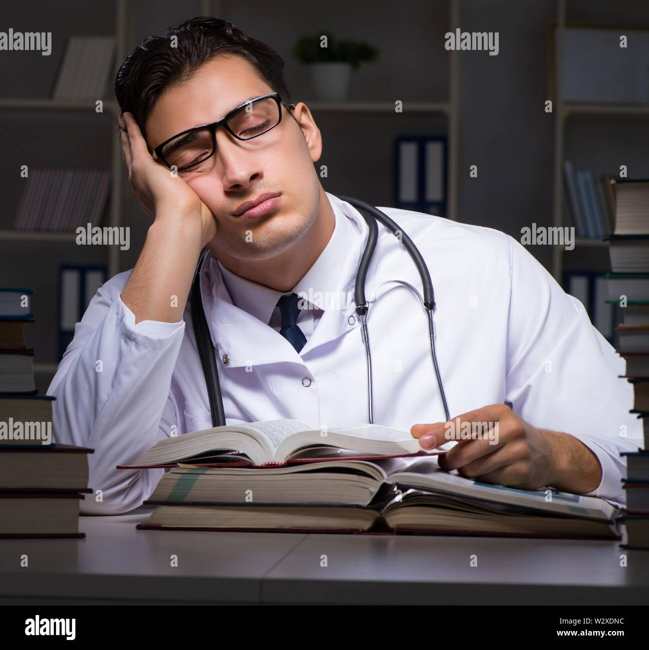The medical student preparing for university exams at night - Stock Image