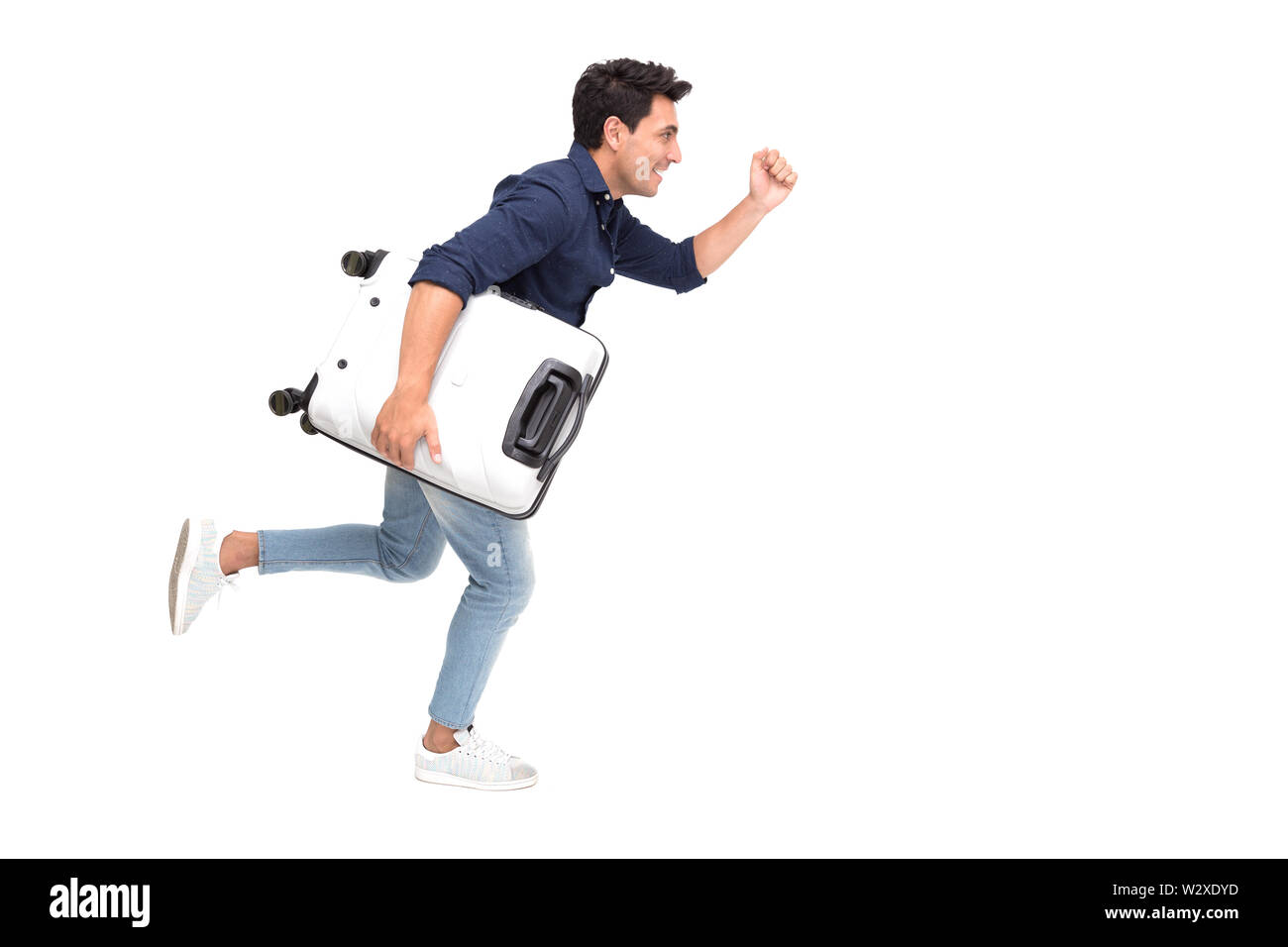 Handsome Caucasian tourist running fast and holding luggage on white background, Vacation travel concept Stock Photo