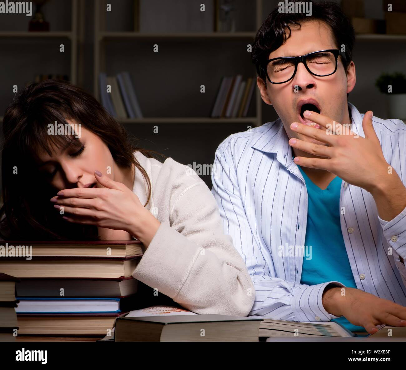 The two students studying late preparing for exams - Stock Image