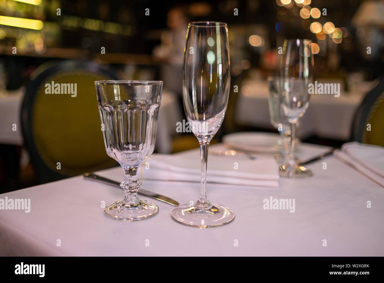 Natural light or daylight shot of modern restaurant table set for a lunch. Shallow focus on wine glass. Empty glasses set in restaurant. Close up phot - Stock Image