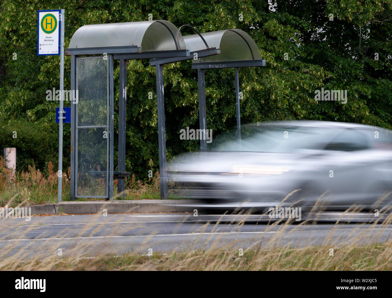 Nauen, Germany. 10th July, 2019. A car drives at a run down bus stop in the forest settlement Weinberg. Credit: Monika Skolimowska/dpa-Zentralbild/dpa/Alamy Live News - Stock Image