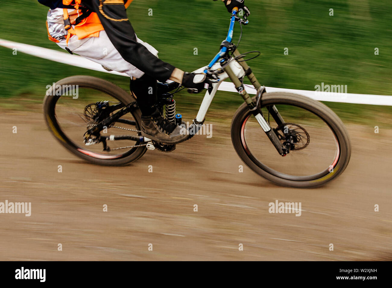 dh rider riding forest trail in downhill motion blur - Stock Image