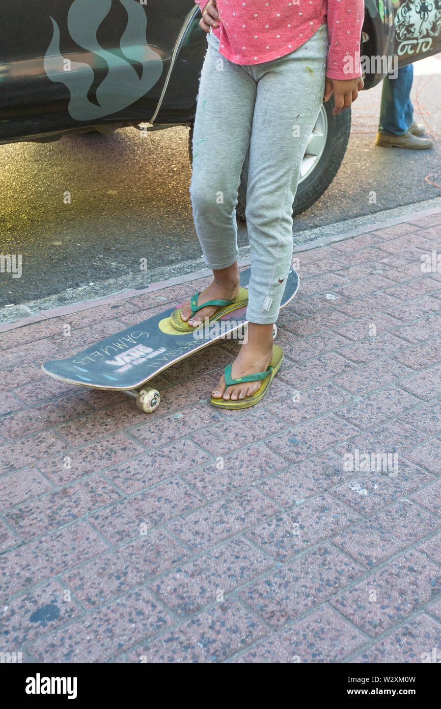 skateboard on a pavement with legs and feet of a female child of mixed blood race standing with one foot on it and poor, impoverished and neglected Stock Photo