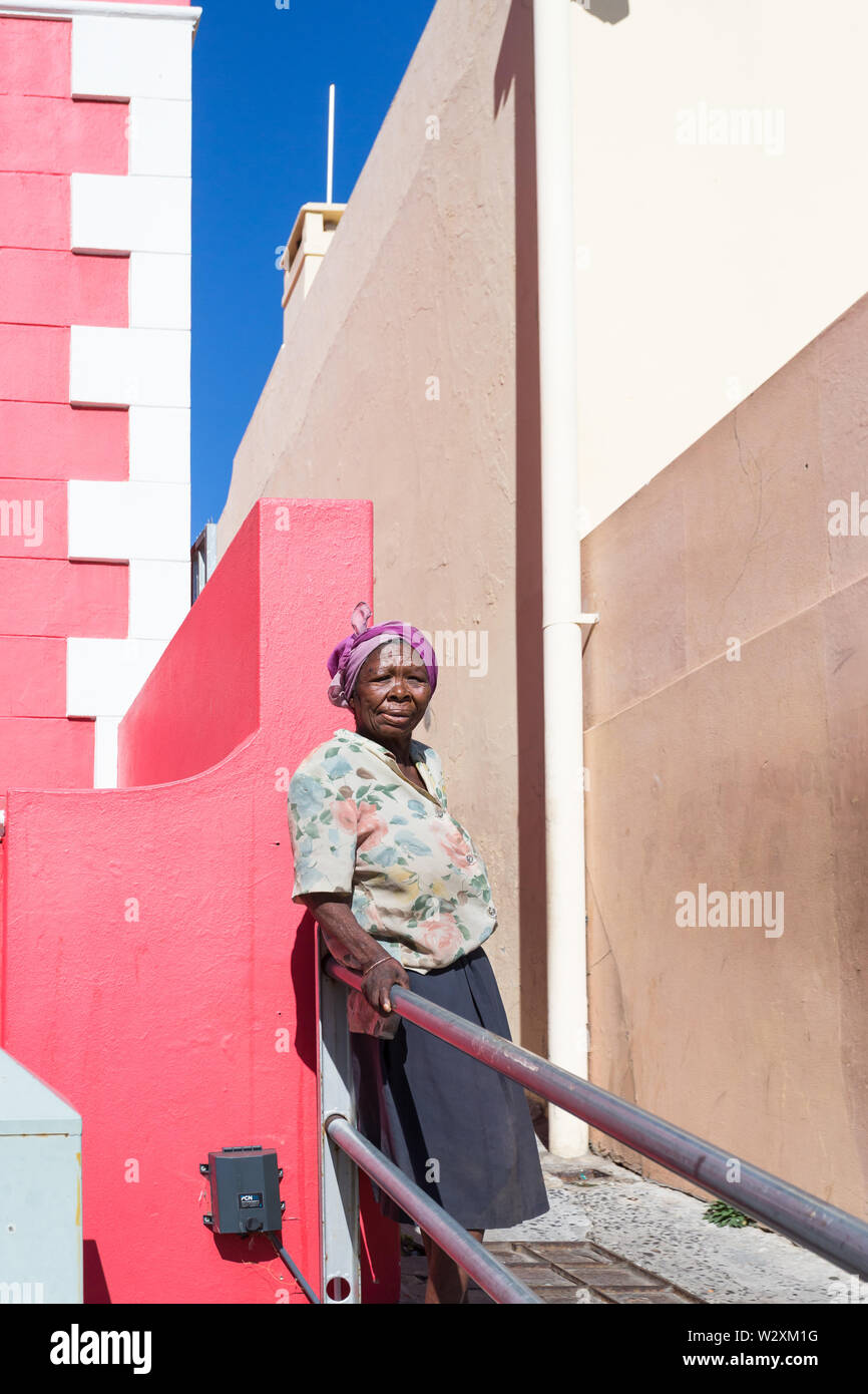 portrait of elderly poor impoverished African black lady or woman leaning against railings at a red coloured wall in Bo Kaap, Cape Town, South Africa - Stock Image