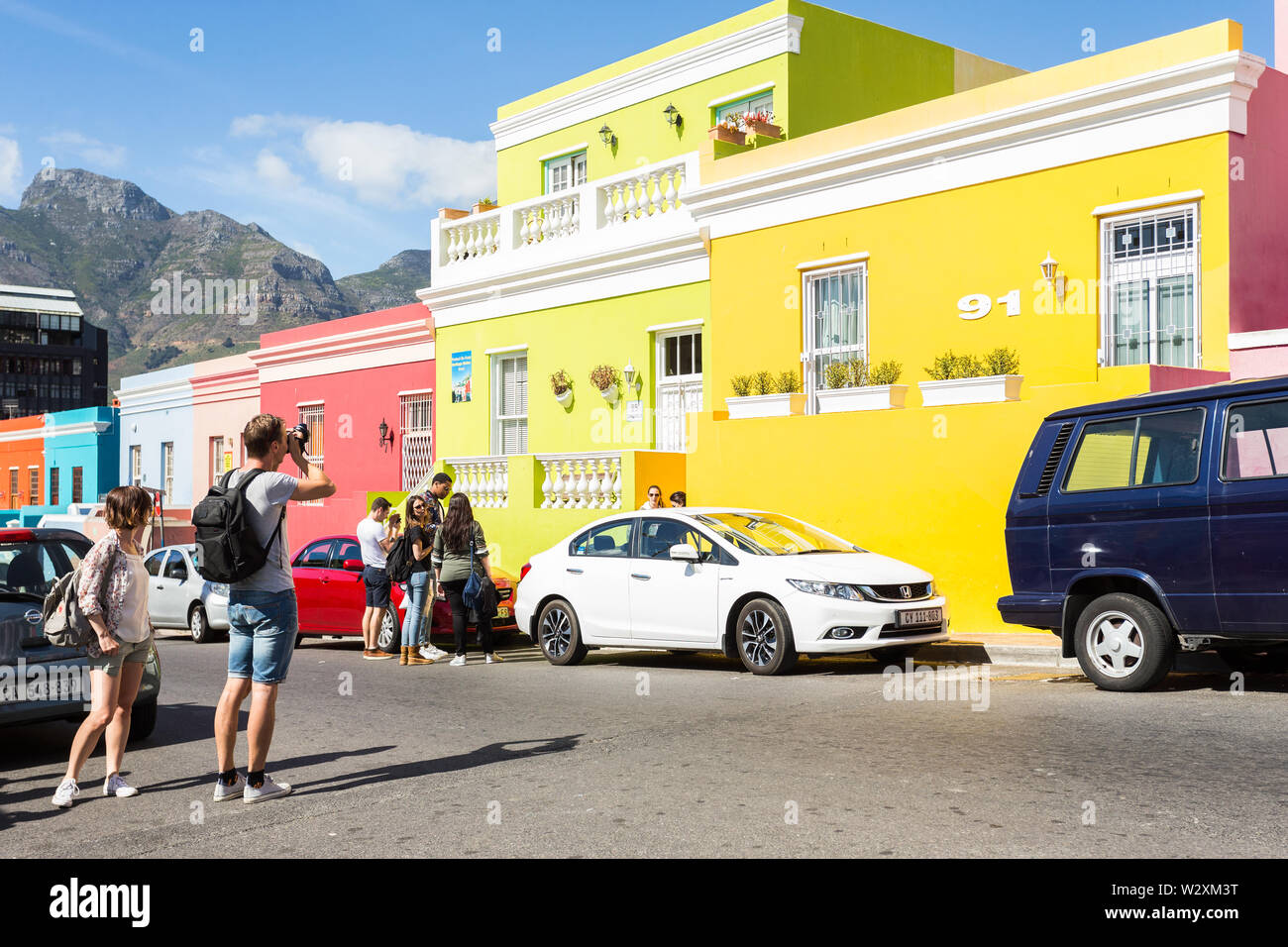 male caucasian tourist taking a photo of a colourful row of houses while standing in a street in Bo Kaap, Cape Town, South Africa while sightseeing Stock Photo