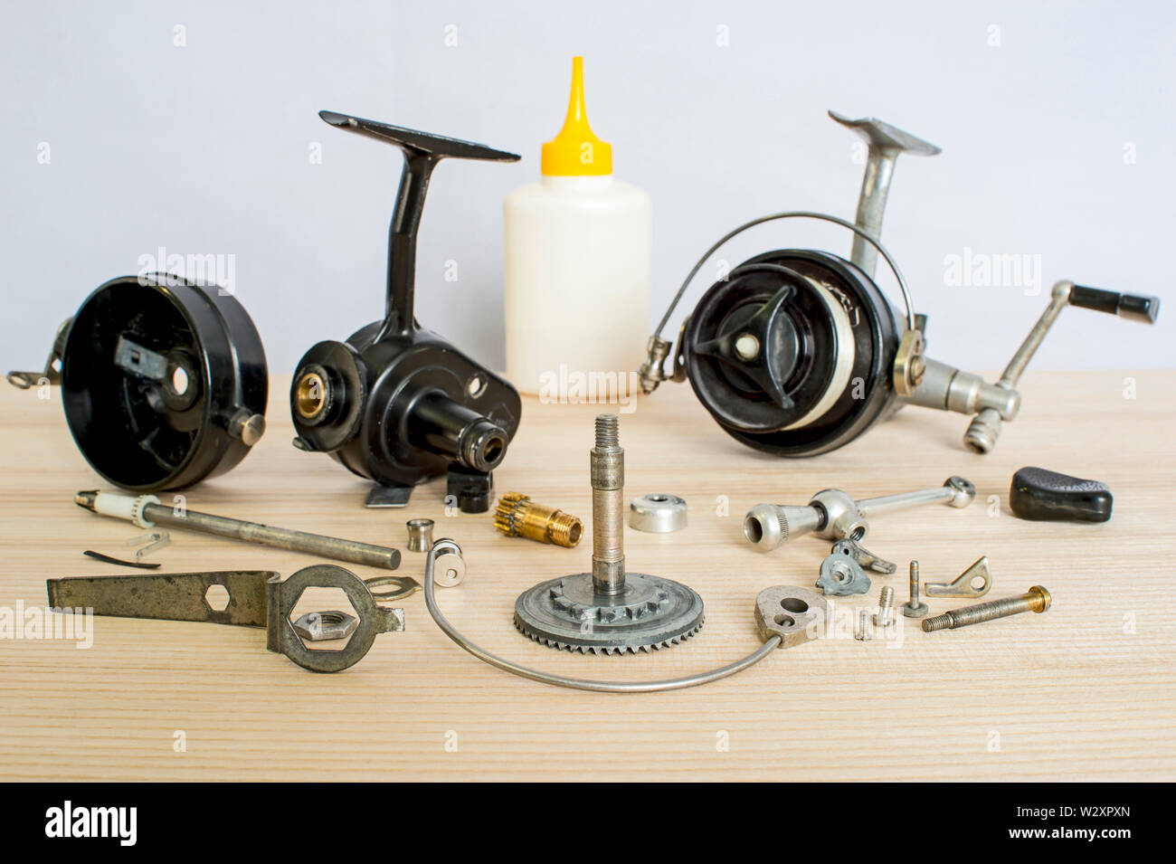 A fishing spinning reel as a whole and a second similar completely disassembled. Concept: parts of a whole. - Stock Image