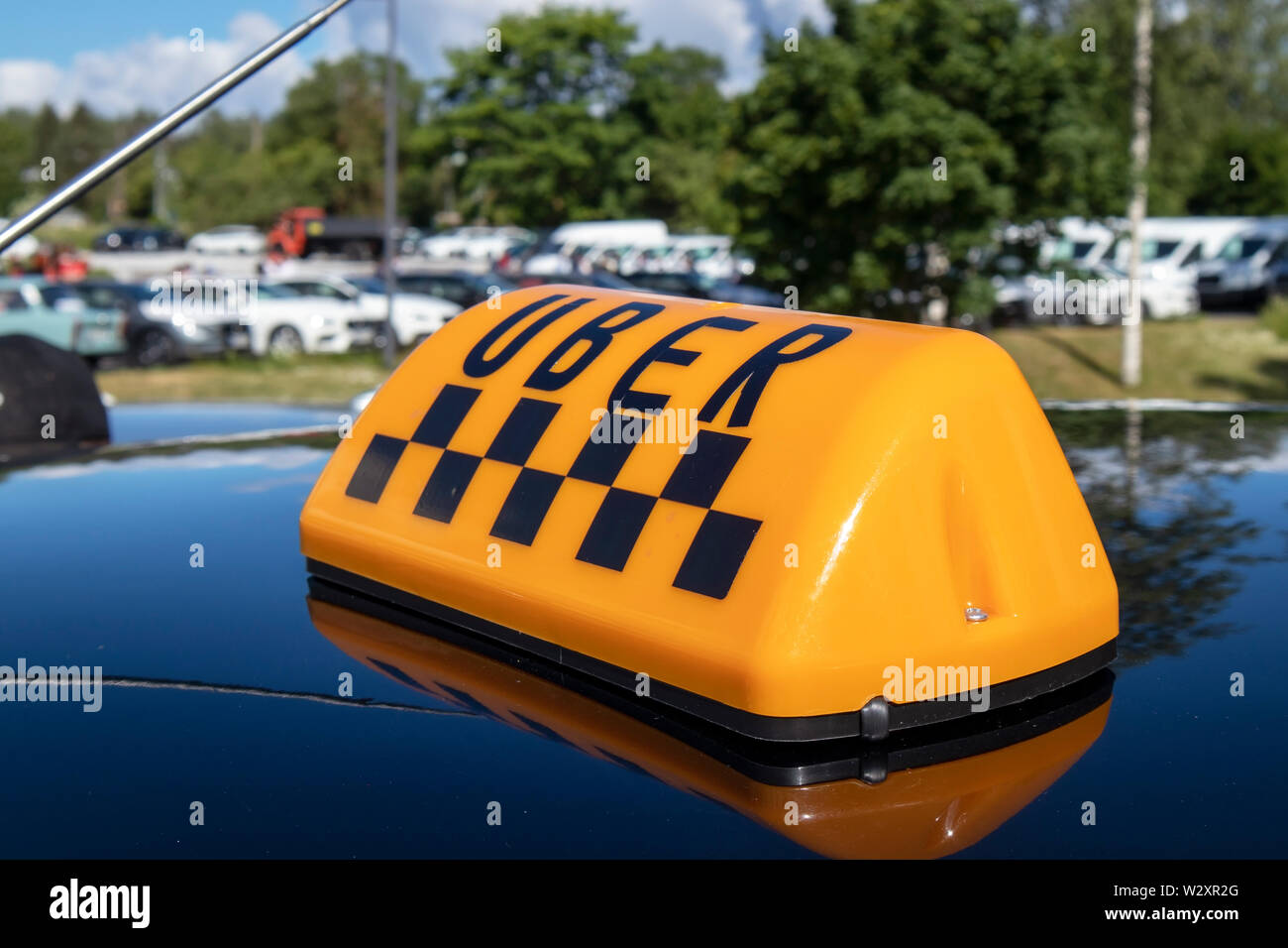 Uber taxi sign on top of a car - Stock Image