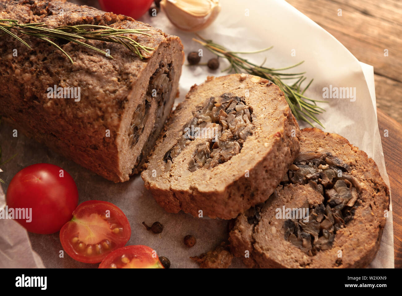 Tasty Meatloaf with mushrooms on wooden table - Stock Image