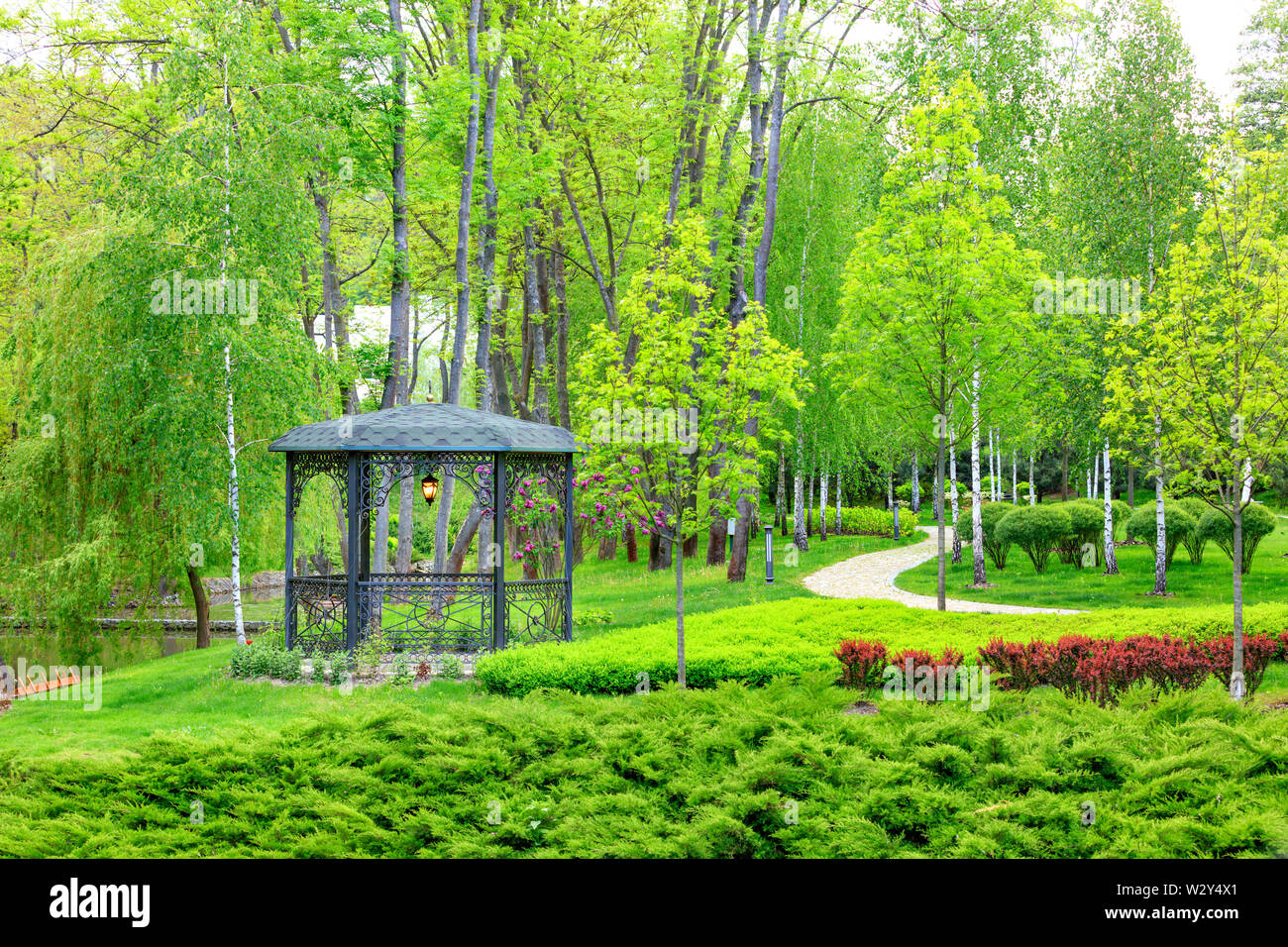 An openwork metal gazebo with a soft lamp in the center stands on a green lawn with decorative flowers, near a paved path passing by, framed on all si - Stock Image