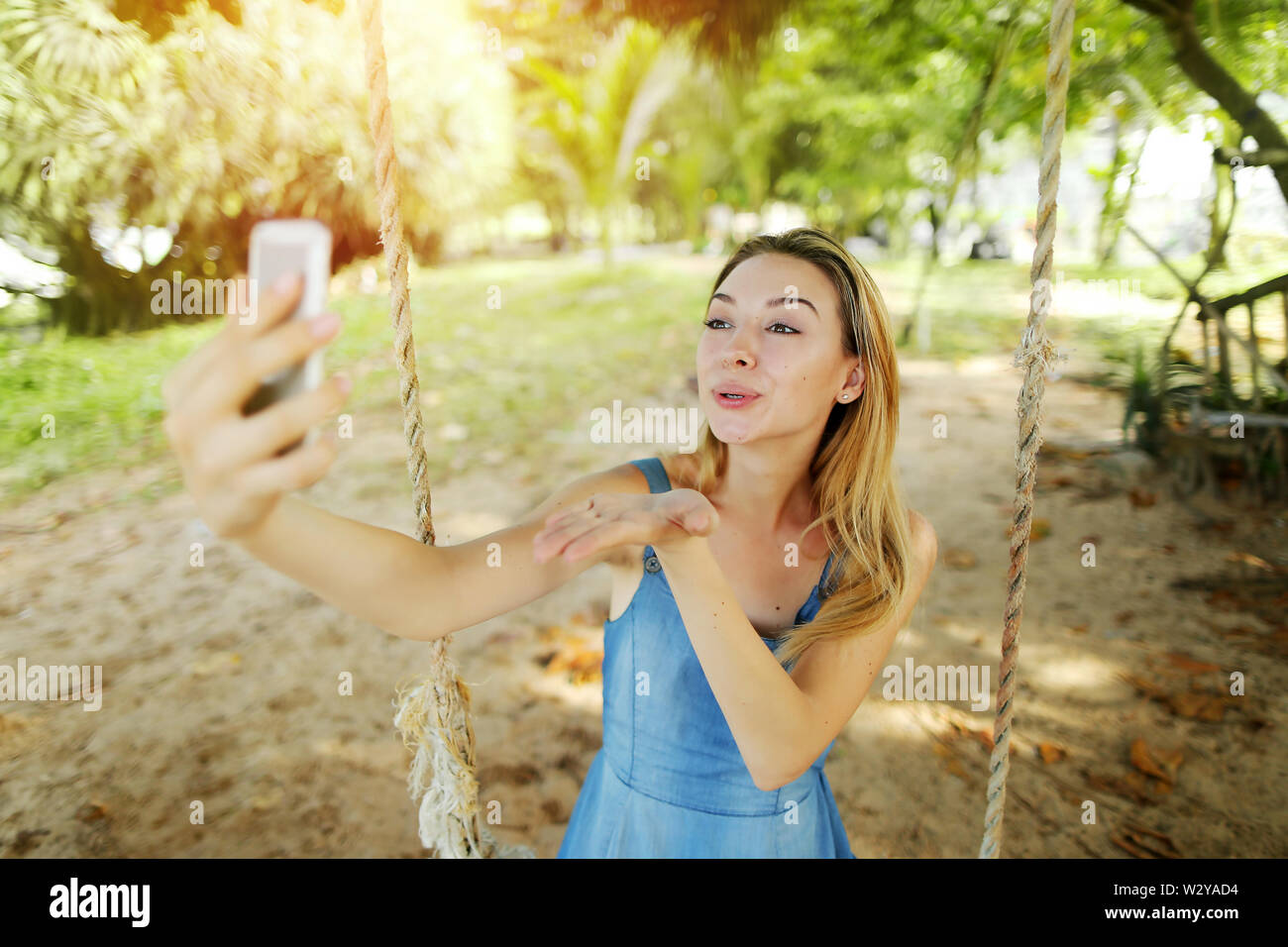 Sunshine photo of young woman making selfie by smartphone and riding swing on sand in Bali. Concept of summer resort in tropical place, modern technol - Stock Image