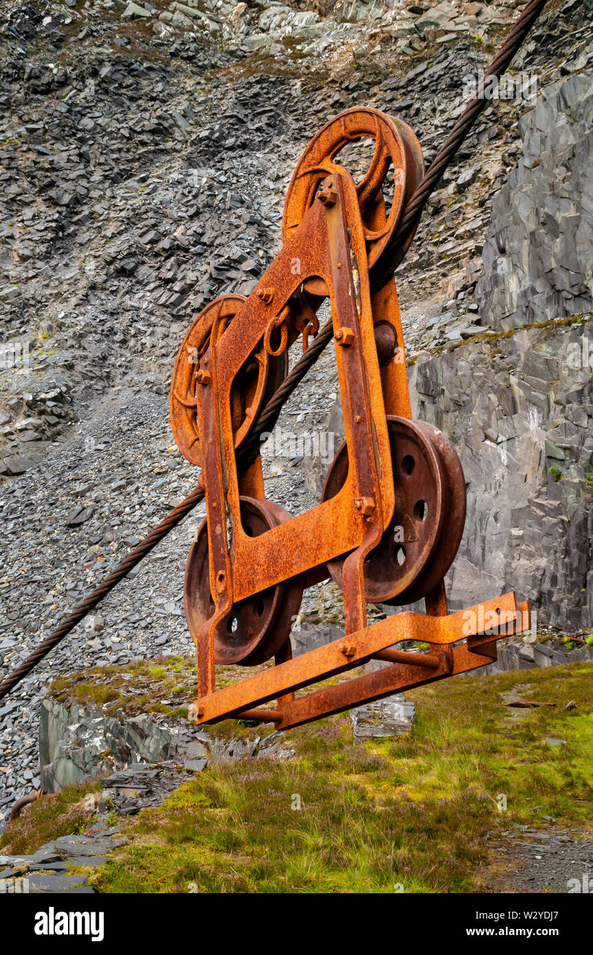 Pulley Block suspended on a steel cable at Dinorwic slate quarry with the working face behind. Stock Photo