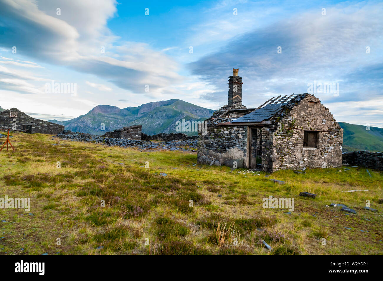 A ruined cottage on a high-level bench at Dinorwic Quarry, with the peak of Snowdon in the background. Stock Photo