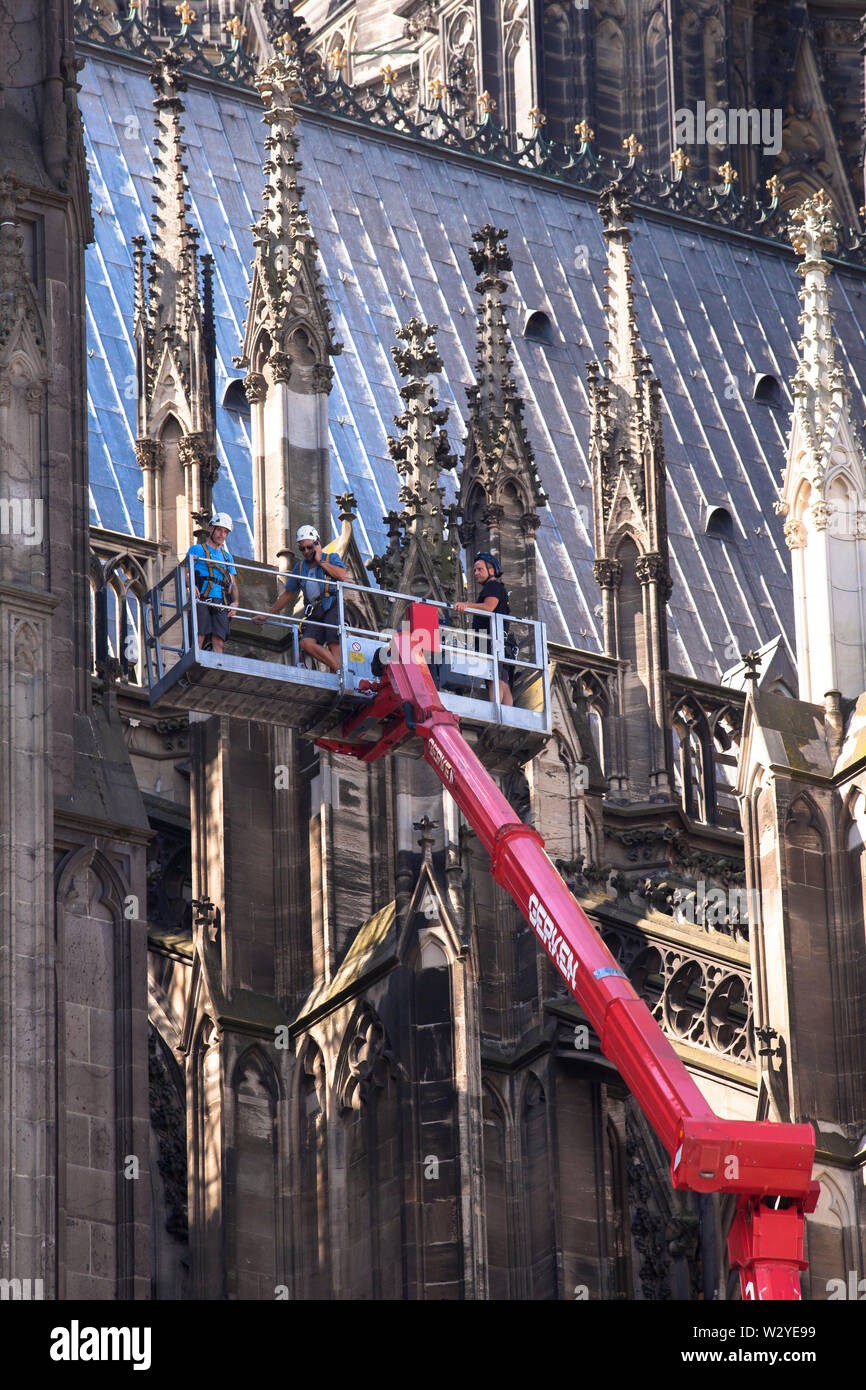 workers on an aerial work platform at the north side of the cathedral, Cologne, Germany.  Arbeiter auf einer LKW-Arbeitsbuehne an der Nordseite des Do - Stock Image