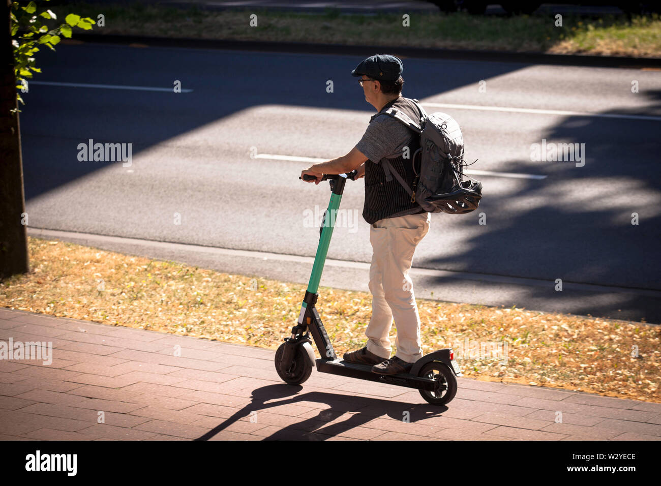 man on a rental electric scooter in the city, Cologne, Germany.  Mann auf Miet-Elektroscooter in der Innenstadt, Koeln, Deutschland. Stock Photo