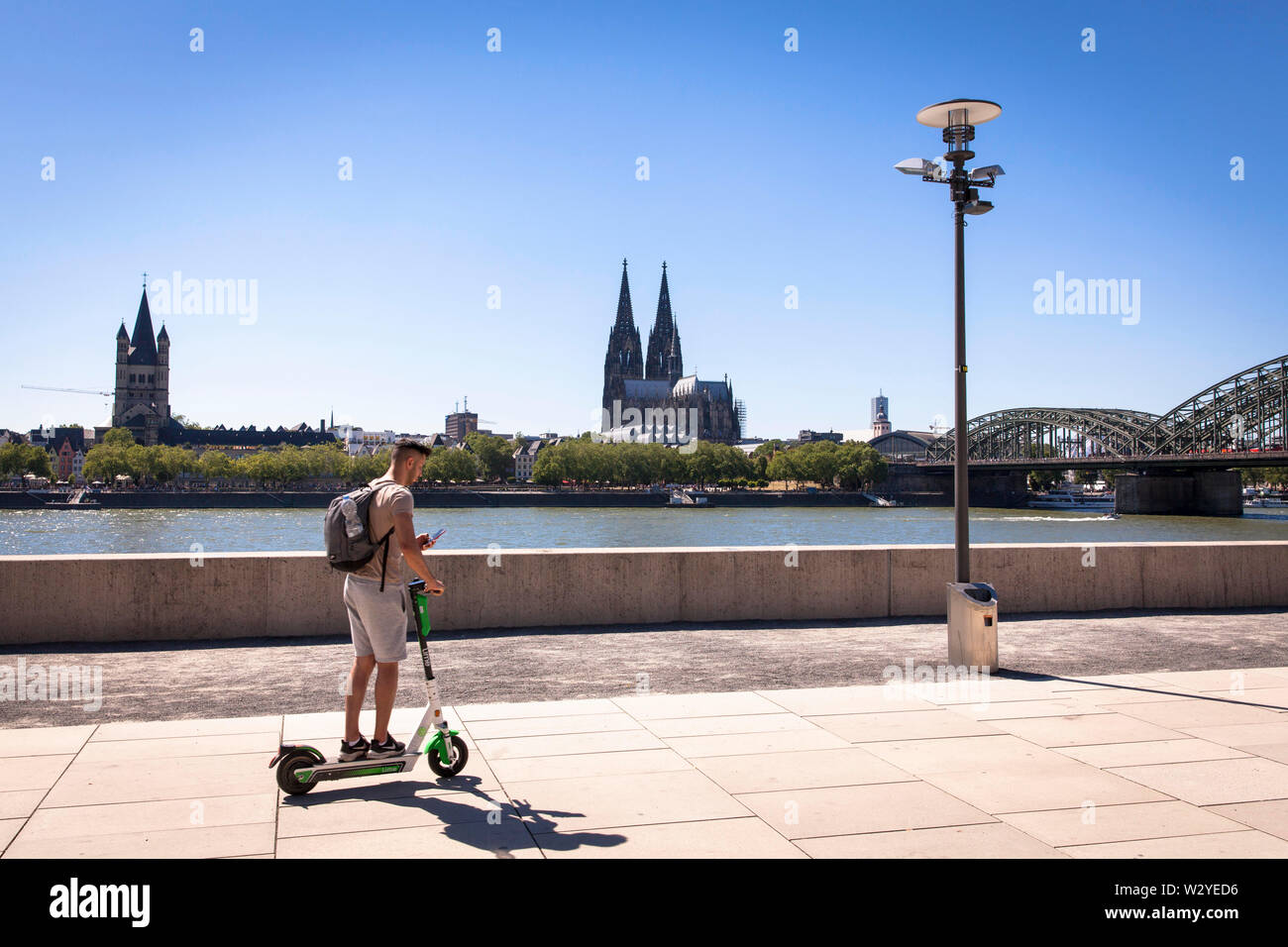man on a rental electric scooter on the banks of the river Rhine in the district Deutz, Cologne, Germany. Church Gross St. Martin and the cathedral. - Stock Image