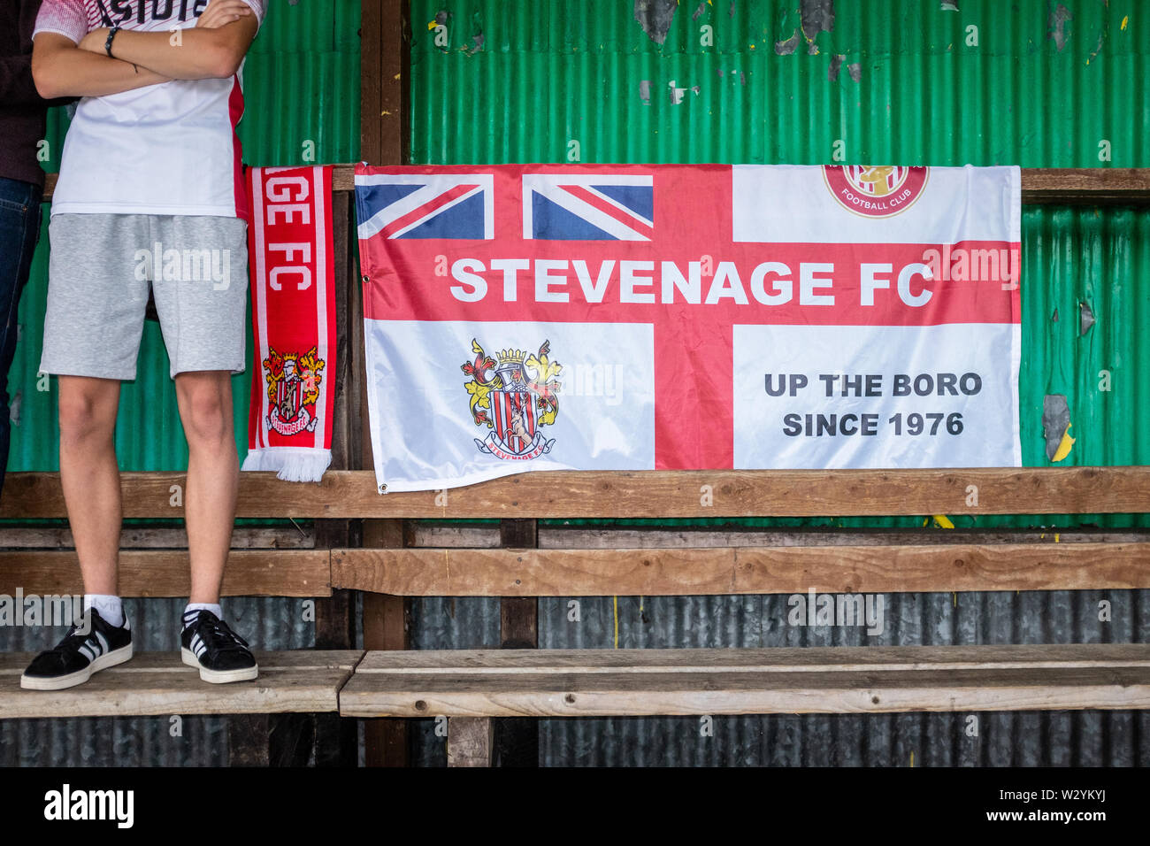 Unidentifiable fan standing beside England flag on terrace during game at football match Stock Photo