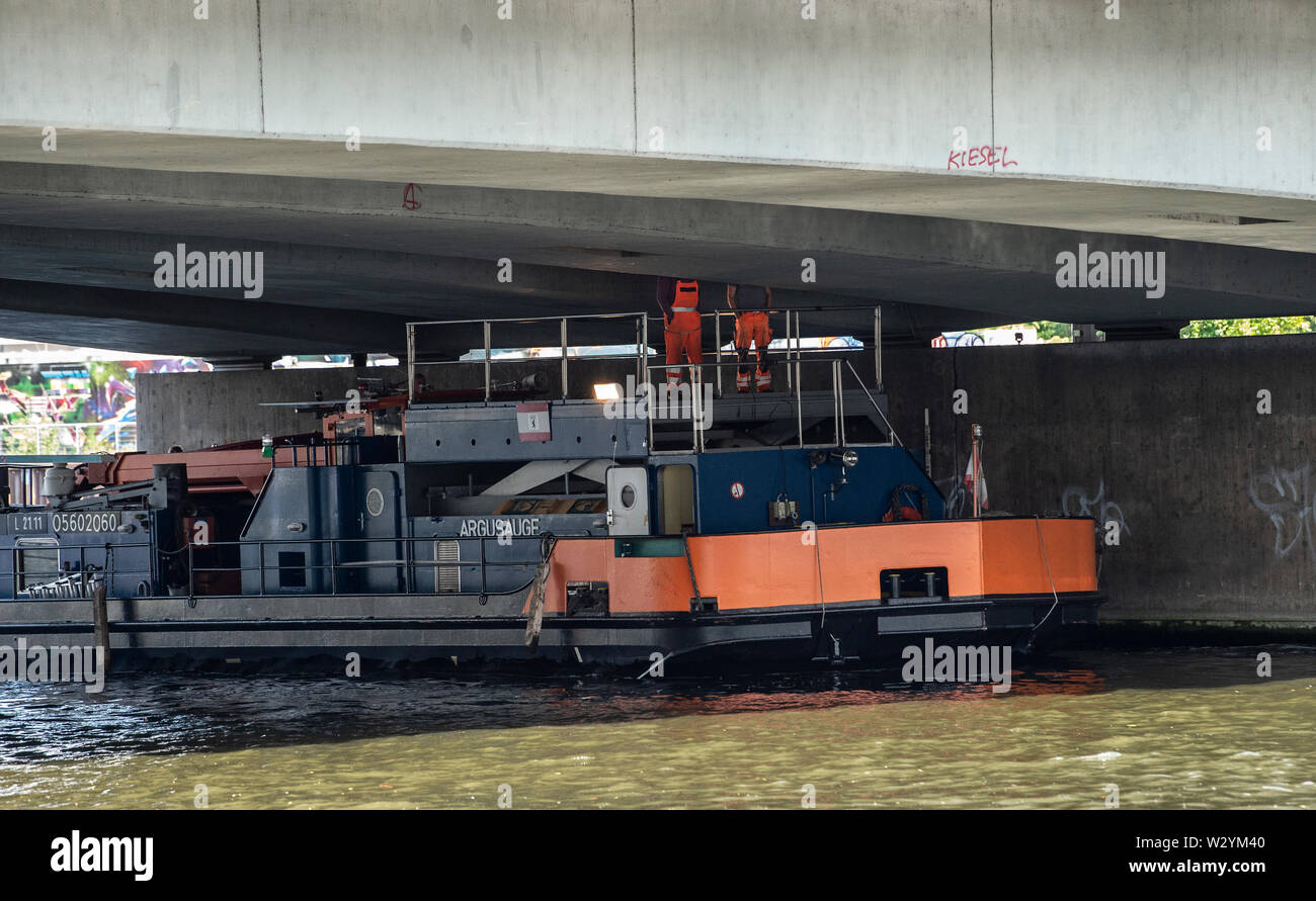 Berlin, Germany. 11th July, 2019. From a ship, workers control the underside of the Elsen Bridge. In the summer of 2018, considerable damage was found to the structure, so that the bridge will be demolished and probably rebuilt by 2028. Part of the bridge has been closed to traffic since 2018. Credit: Paul Zinken/dpa/ZB/dpa/Alamy Live News - Stock Image