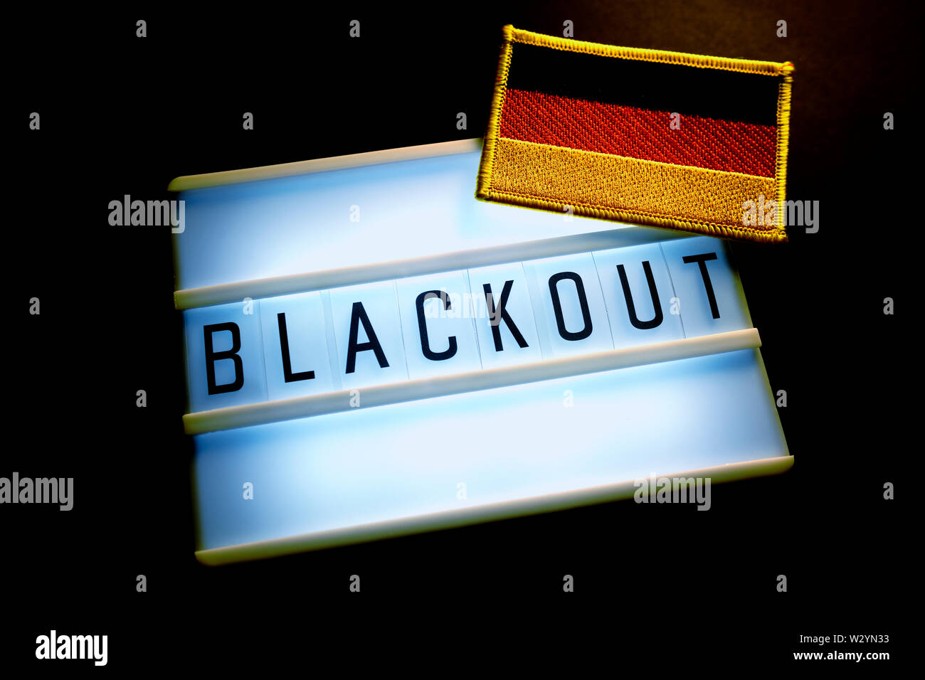 The word blackout on an illuminated panel and flag of Germany, power failure - Stock Image