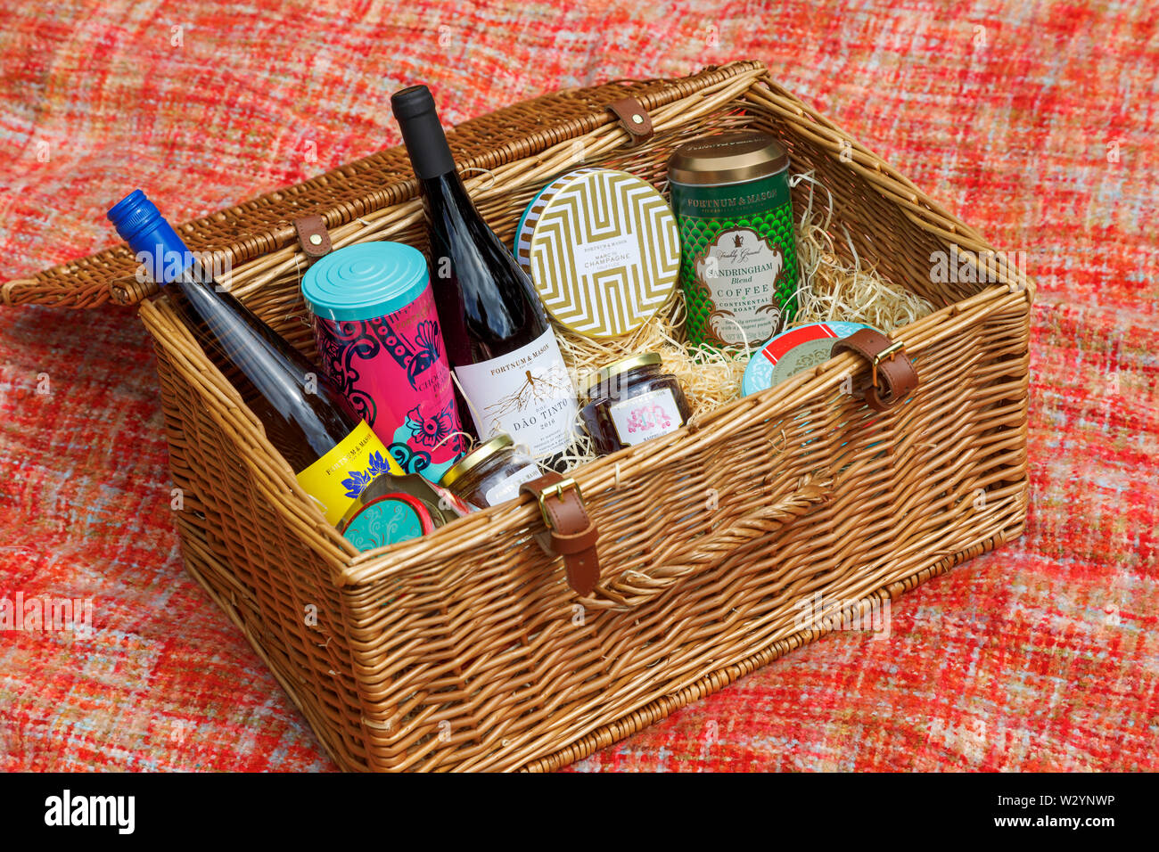 Luxury lifestyle: Fortnum & Mason wicker picnic hamper (the Grosvenor Hamper) with an open displaying contents on a red woollen rug - Stock Image