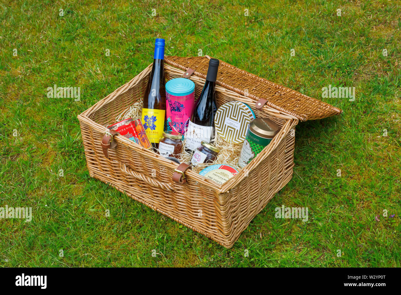 Luxurious lifestyle: Fortnum & Mason wicker picnic hamper (the Grosvenor Hamper) on grass with an open top displaying contents - Stock Image