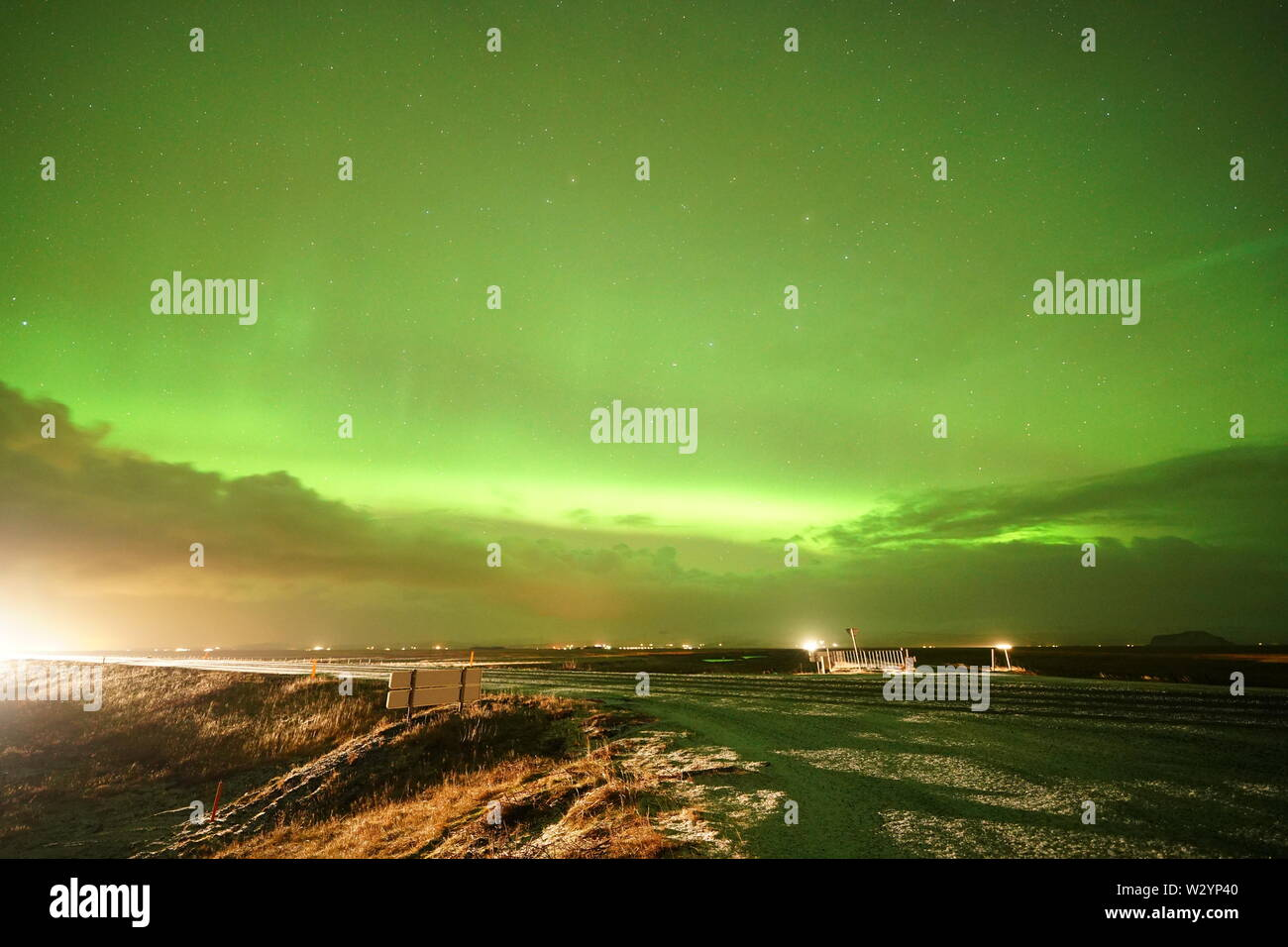 Strong Northern lights in Iceland on the road - Stock Image
