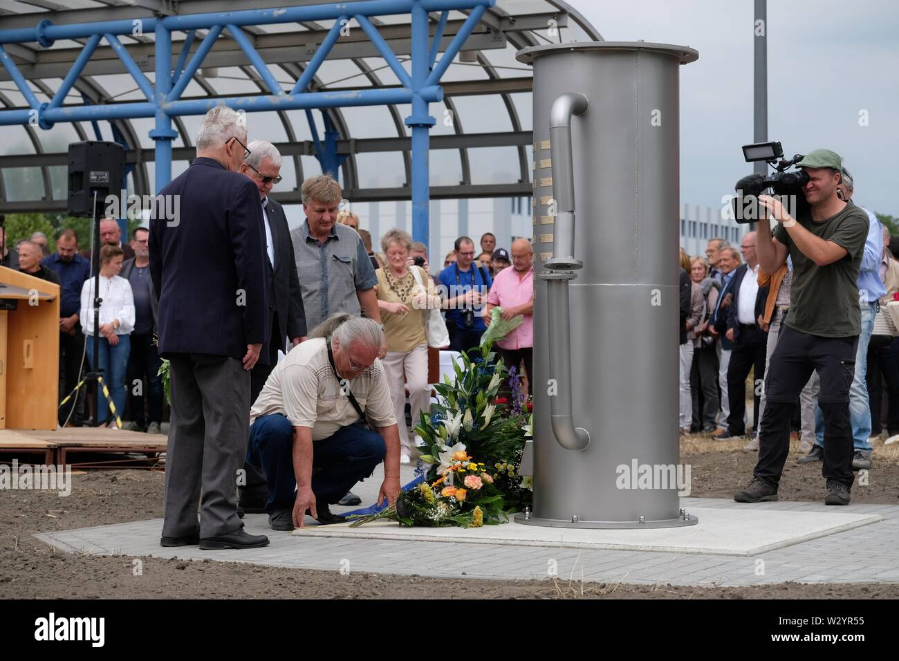 Bitterfeld Wolfen, Germany. 11th July, 2019. Participants in a commemoration ceremony place flowers at a monument in the Chemical Park. A stele commemorates the victims of the chemical accident of 11.07.1968, when 40 people died and more than 240 were injured. Credit: Sebastian Willnow/dpa-Zentralbild/ZB/dpa/Alamy Live News - Stock Image