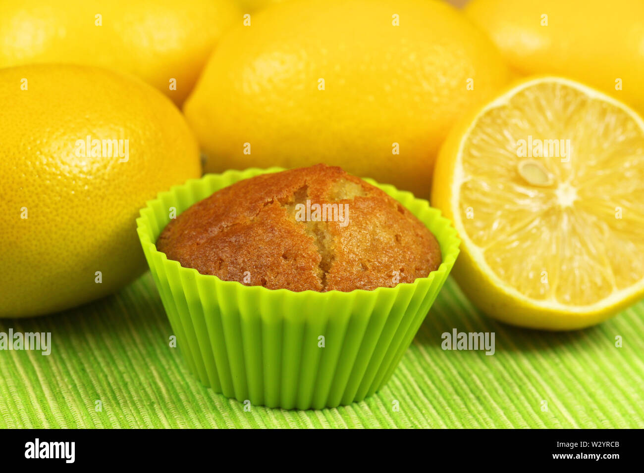 Lemon mufin in green cupcake with whole yellow lemons - Stock Image