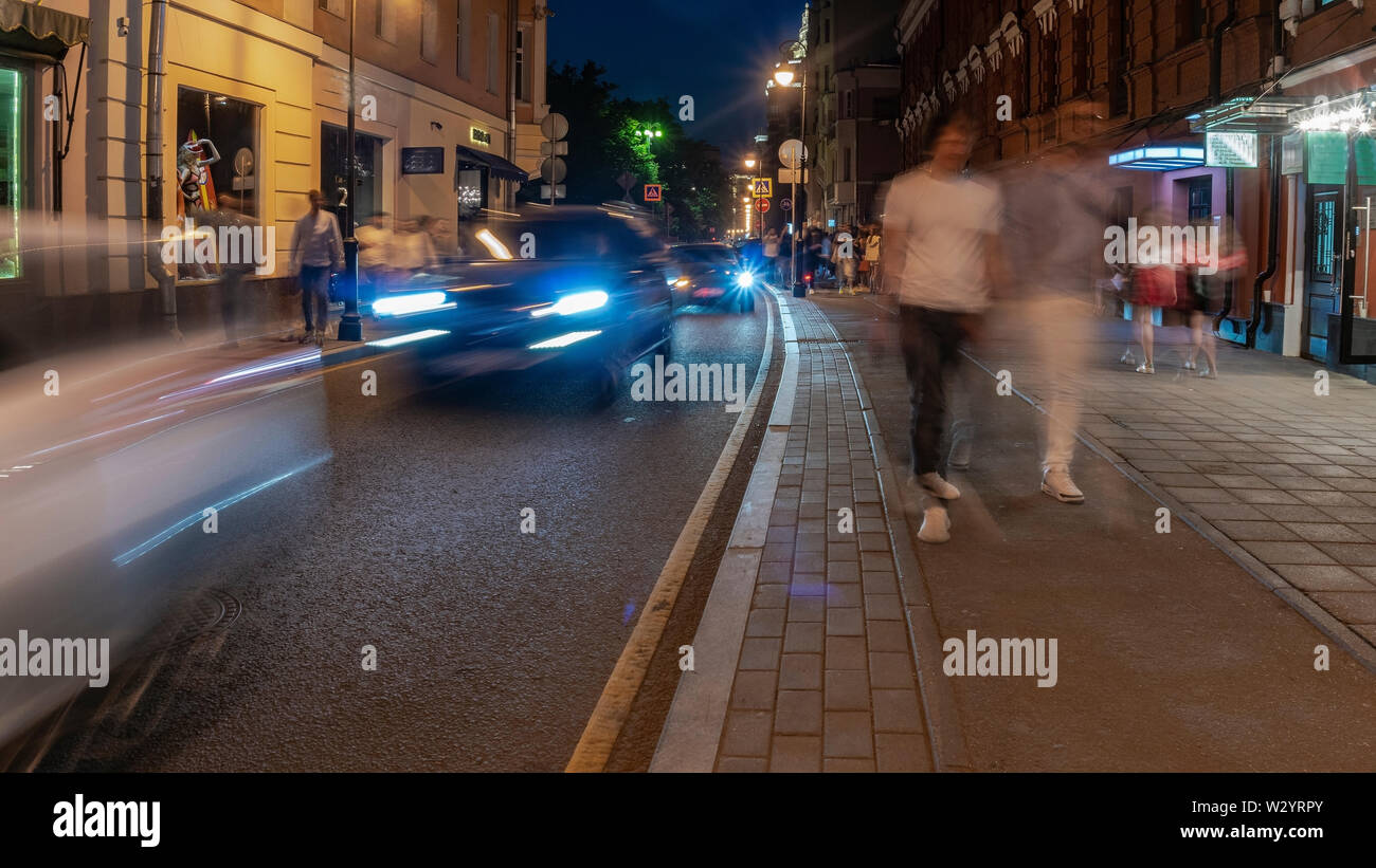 the flow of people and cars on a narrow street in the city center, in Saturday night - Stock Image