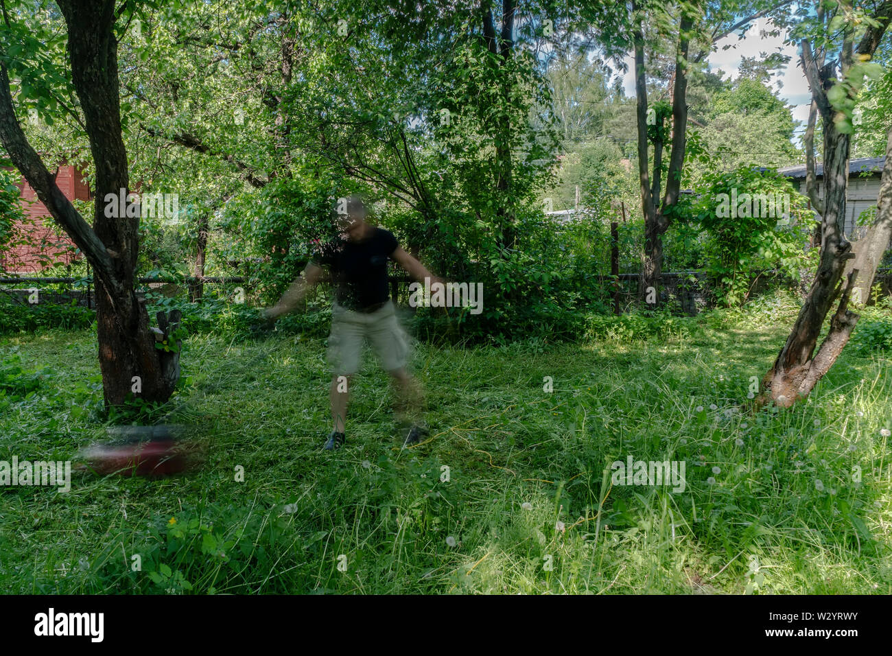 Aged Man cutting grass in the overgrown garden, - Stock Image