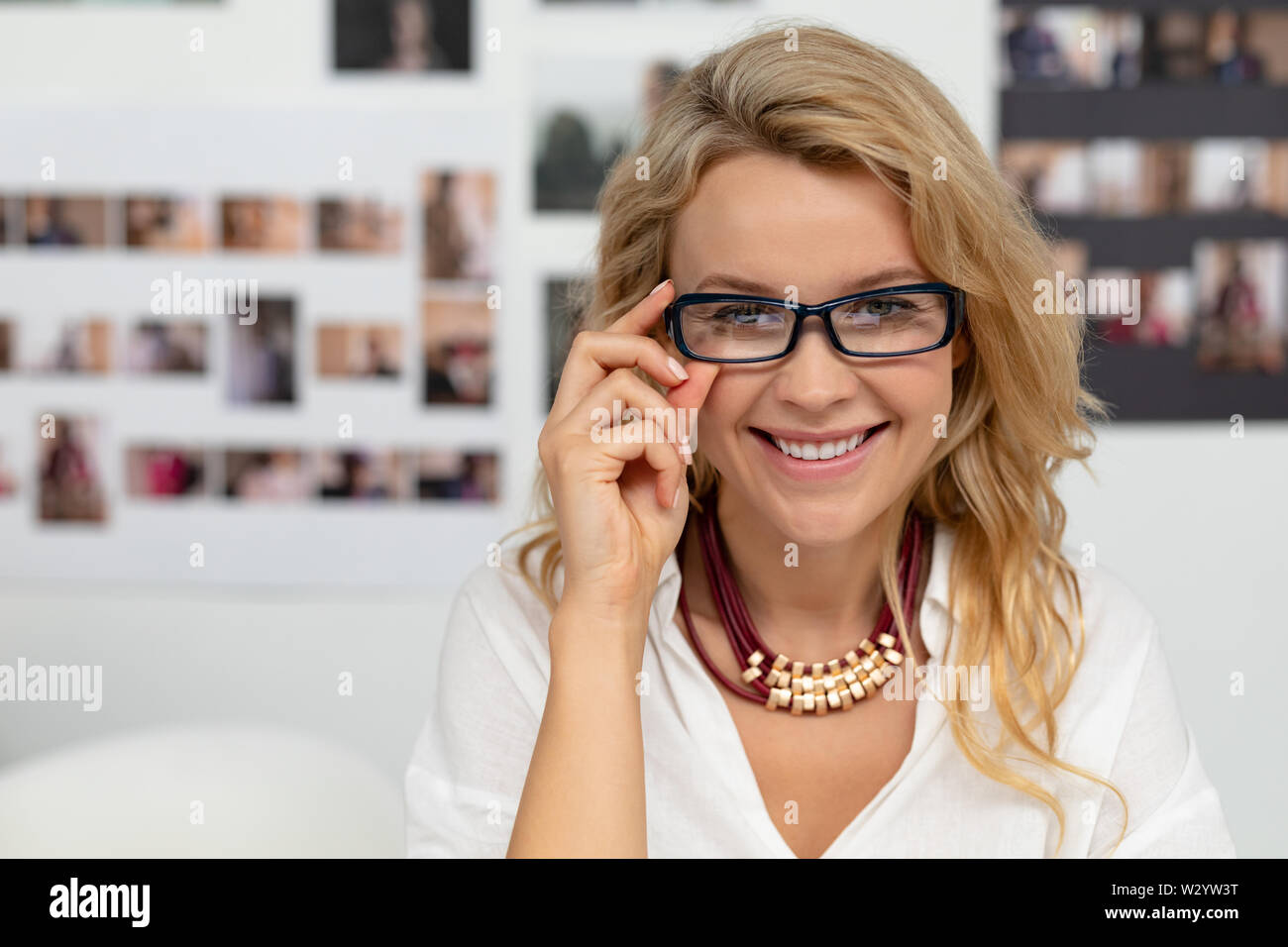 Happy female graphic designer adjusting her spectacle in office - Stock Image