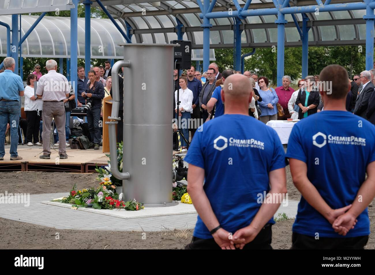 11 July 2019, Saxony-Anhalt, Bitterfeld-Wolfen: Participants in a commemoration ceremony stand at a monument in the Chemical Park. A stele commemorates the victims of the chemical accident of 11.07.1968, when 42 people died and more than 240 were injured. Photo: Sebastian Willnow/dpa-Zentralbild/ZB - Stock Image