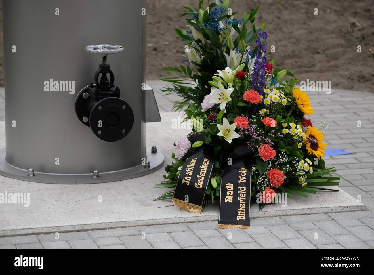 11 July 2019, Saxony-Anhalt, Bitterfeld-Wolfen: A wreath lies at a memorial ceremony at the chemical park at a monument. A stele commemorates the victims of the chemical accident of 11.07.1968, when 42 people died and more than 240 were injured. Photo: Sebastian Willnow/dpa-Zentralbild/ZB - Stock Image