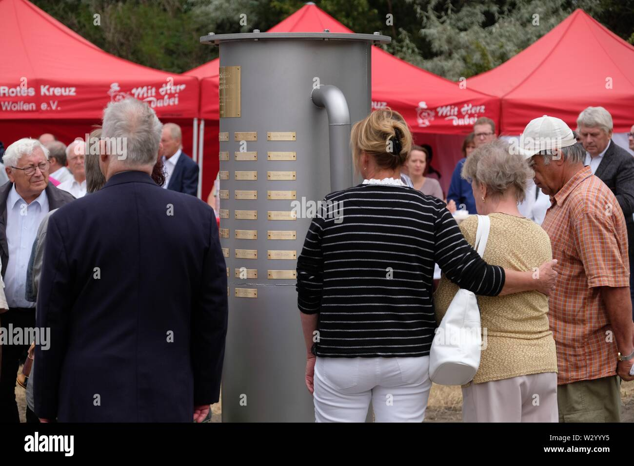 11 July 2019, Saxony-Anhalt, Bitterfeld-Wolfen: Participants in a commemoration ceremony stand at a monument in the Chemical Park. A stele commemorates the victims of the chemical accident of 11.07.1968, when 42 people died and more than 270 were injured. Photo: Sebastian Willnow/dpa-Zentralbild/dpa - Stock Image