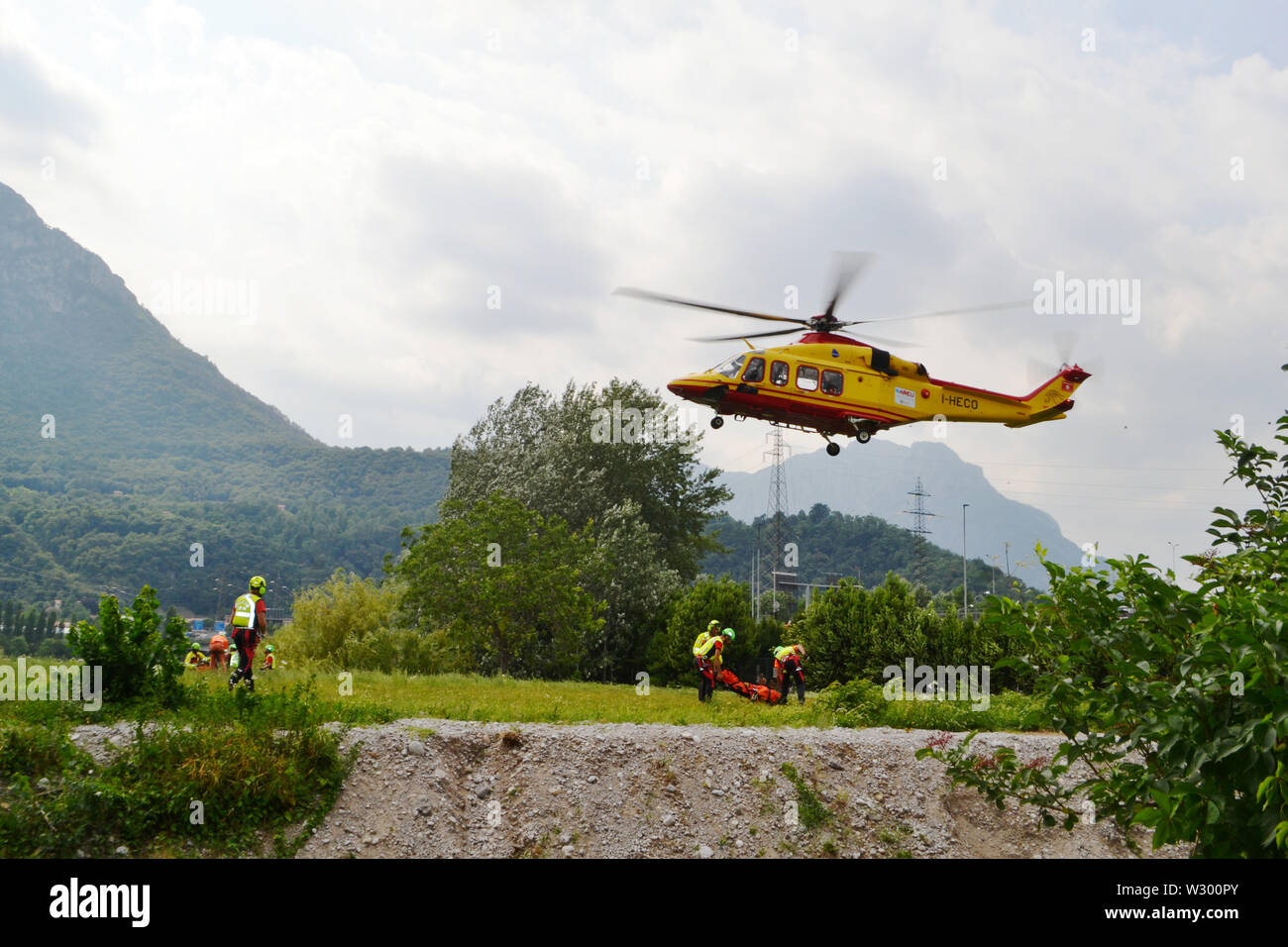 Lecco/Italy - July 10, 2019: Members of the National Alpine rescue team of Lecco are exercising in rescue with the help of helicopter service. Stock Photo
